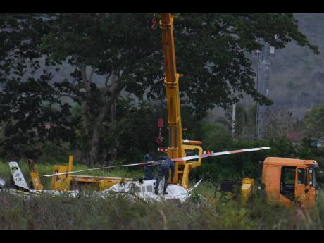 Jamaica Defence Force personnel attaching the helicopter to a crane for it to be lifted on to the back of a flatbed truck for transportation to Kingston after the student-flown aircraft landed in a farm in Dunbeholden, St Catherine, yesterday. No serious i
