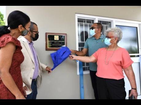 Minister of Health and Wellness Dr Christopher Tufton (second right), unveils the plaque to officially open the Kenneth Baugh Health Centre in Point Hill, St Catherine, on Wednesday, June 9. Looking on are Baugh's widow, Vilma (right), and his children,