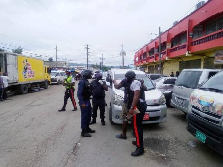 In this file photo, police personnel are seen patrolling in downtown Montego Bay, St James.