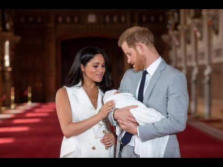 Britain's Prince Harry and Meghan, Duchess of Sussex, pose during a photocall with their then newborn son Archie, in St George's Hall at Windsor Castle on May 8, 2019. Markle's 'The Bench' celebrates the bond between Prince Harry and Archie, and