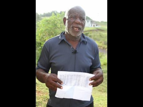 Edward Anderson, a residents of Bethel Isles, Manchester, displays a document given to him by bauxite company Jamalco indicating the lots that belong to him.