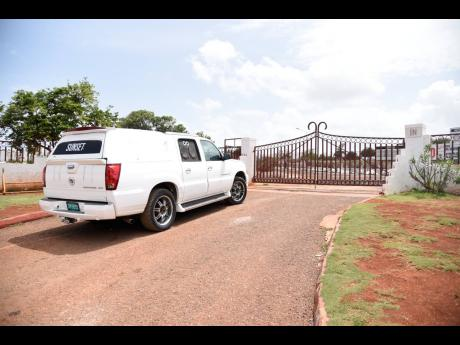 A hearse parked in front of the closed gate of Meadowrest Memorial Gardens after burial workers walked off the job on Thursday.