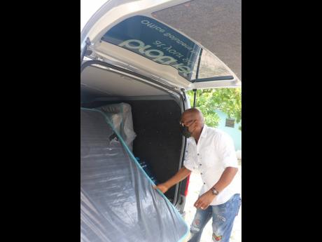 Reggae singer George Nooks helps to unload the mattresses he donated to the golden-age home in Kingston.