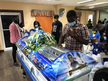 Keithy Simpson (right), a former club teammate of Tremaine Stewart, pays his last respects to the former national footballer at his funeral service held at Perry's Funeral Home in Spanish Town yesterday.