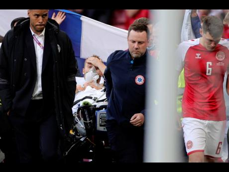 Paramedics using a stretcher to take out of the pitch Denmark's Christian Eriksen after he collapsed during the Euro 2020 championship group B match between Denmark and Finland at Parken stadium in Copenhagen, Denmark, Saturday, June 12, 2021.