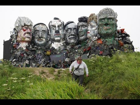 A visitor walks away from a sculpture created out of e-waste in the likeness of Mount Rushmore and the G7 leaders on a hill in Hayle, Cornwall, England.