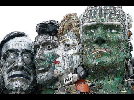 A sculpture created out of e-waste in the likeness of Mount Rushmore and the G7 leaders stands on a hill in Hayle, Cornwall, England, Wednesday, June 9, 2021. The sculpture, created by British artist Joe Rush ad sculptor Alex Wreckage, named Mount Recyclem