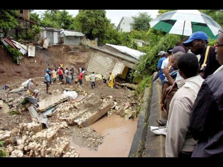 Anxious residents of Sandy Park in St Andrew look on as a team digs through silt and debris in search of six family members who were washed away when their house collapsed into the waterway in September 2010.