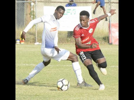 Cordel Benbow (right) from Mount Pleasant United evades a tackle from Chavany Willis from Portmore United during their Red Stripe Premier League football match at the Spanish Town Prison Oval on Sunday, January 6, 2019.