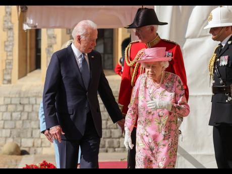 Britain's Queen Elizabeth II walks with US President Joe Biden during his visit to Windsor Castle yesterday.