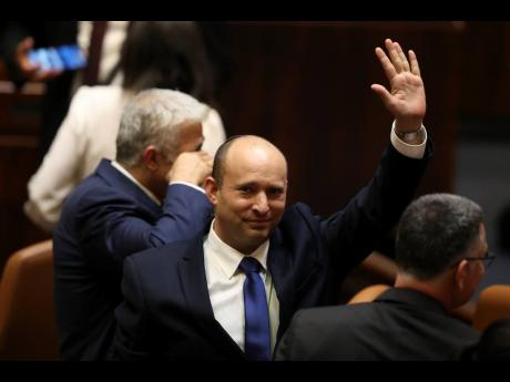 Israel's new prime minister, Naftali Bennett, raises his hand during a Knesset session in Jerusalem yesterday.