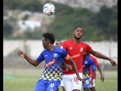 Molynes United's Nicholas Nelson (left) goes up for a header with UWI FC's Sheldon McKoy during their Jamaica Premier League encounter at the UWI Mona Bowl on Sunday, January 26, 2020.