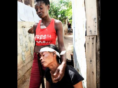 Aretha Ellison (seated), mother of Damoya Hall, grieves Sunday's killing of the teenager while being comforted by Shelly-Ann Turner, a resident of Third Street in Trench Town.