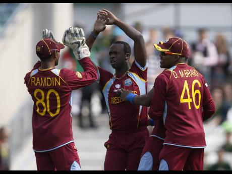West Indies' players celebrate the wicket of Pakistan's Imran Farhat during their ICC Champions Trophy Group B match at the Oval cricket ground, London, in June 2013.
