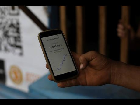 A worker at Hope House, an organisation that sponsors the use of cryptocurrencies in El Zonte beach, makes a purchase at a small store that accepts bitcoin, in Tamanique, El Salvador, on June 9, 2021.