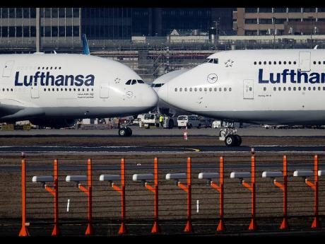In this February 14, 2019 file photo, an Airbus A380, left, and a Boeing 747, both from Lufthansa airline, pass each other at the airport in Frankfurt, Germany.
