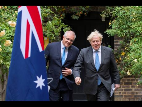 Prime Minister of Australia Scott Morrison, left, walks with Prime Minister of the United Kingdom Boris Johnson after their meeting, in the garden of 10 Downing Street, in London, Tuesday June 15, 2021.