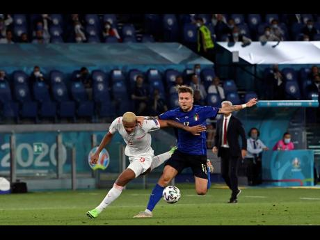 Italy's Ciro Immobile (right) in action against Switzerland's Manuel Akanji during the Euro 2020 championship Group A match between Italy and Switzerland at Olympic stadium in Rome, yesterday. Italy won 3-0.