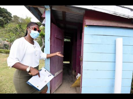 Mellesha Pinto, teacher at the Hall's Delight Primary School, shows the pit latrine that children had to use at the school before the handover of modern facilities.