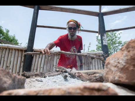 Rudolph Bailey, also known as Ras Kremlin, chairman, Dreaded Nyabinghi Military Council, adds dried wood to the fire in the tabernacle, which is currently in need of repairs as it currently lacks it thatch roof, at the celebrations in Pinnacle, St Catherin