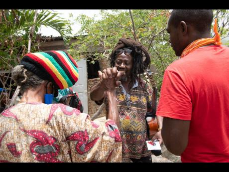 Ras Drick-I (centre) greets a group on arrival at Pinnacle on Wednesday. They were among numerous Rastafarians who visited the area to celebrate the anniversary of the birth of Leonard Howell.