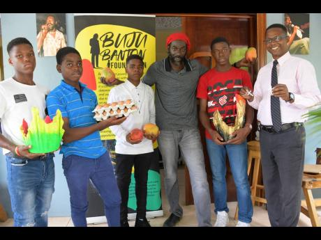 Residents of the Sunbeam Children's Home and their administrator, Desmond Whitely (right), came to Gargamel Music Inc. bearing gifts, including two large pottery vases and eggs from their Layers Project for Buju Banton.