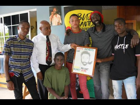 Residents of the Mount Olivet Boys' Home, Patrick Newman (second right), director of the home and Buju Banton (second right), following the presentation of a portrait, drawn by the boys, to Banton.