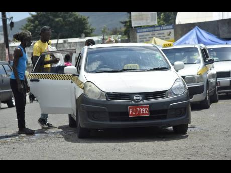 In this March 2020 photo passengers are seen boarding a taxi in Papine.