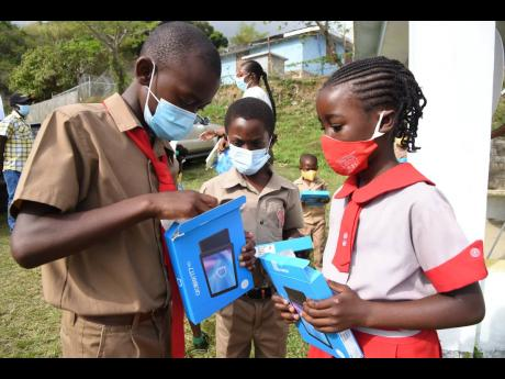 From left: Javian Dormer, Kashan Sterling and Tessan Taylor, students at the Halls Delight Primary and Junior High School in St Andrew East Rural, could hardly wait to open their new tablet computers after they received them from Fayval Williams, minister