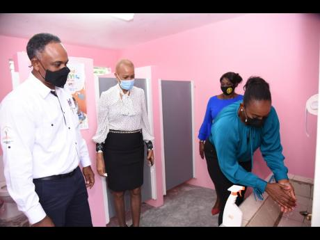 Member of Parliament for East Rural St Andrew  Juliet Holness (right) washes her hands at one of the washbasins in the new sanitation block at the Westphalia Primary School on June 10.  Looking on (from left) are Managing Director of JSIF Omar Sweeney; Min
