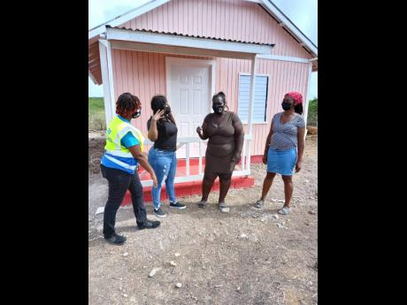 From left: Kivette Silvera, executive director, Food For The Poor; Keteisha McHugh, brand manager, BOOM Energy Drink, presenting Cislyn Williams with the keys to her home. Looking on is Cisyln's mother, Joan Williams.