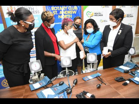Dr Maolynne Miller (third left), founder/chair of the Jamaica Kidney Kids Foundation, demonstrates the new cuffs to be distributed to paediatric departments at 15 hospitals, donated by the Rotary Club of St Andrew North, to Dr Michelle Ann Richards Dawson