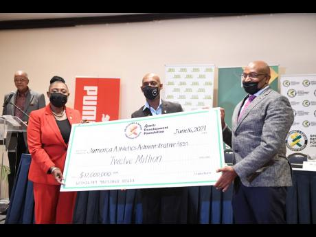 Sport Minister Olivia Grange (left) makes a presentation of a ceremonial cheque for $12million to Jamaica Athletics Administrative Association President Garth Gayle (centre), and National Senior and Junior Championships Organising Committee Chairman Ludlow