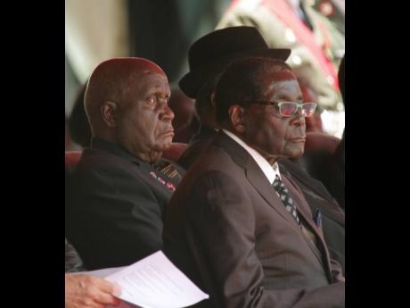 Zambia President Kenneth Kaunda (left) and Zimbabwe President Robert Mugabe attend the funeral of the late Zambia President Michael Sata in Lusaka in November 2014.