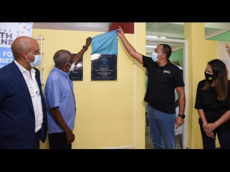 Minister of Health and Wellness Dr Christopher Tufton (third left) unveils a plaque marking the adoption of the Seaforth Health Centre in St Thomas with Norman McDonald, chairman and CEO of Canco Limited, yesterday. At left is St Thomas Western Member of P