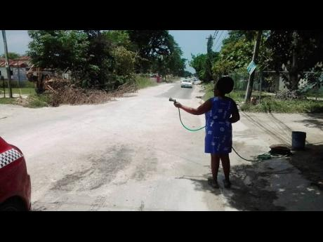 A resident sprays water on the exposed marl to lessen the dust nuisance along the recently paved roadway in Chantilly, Westmoreland, which was damaged less than a week after being handed over.