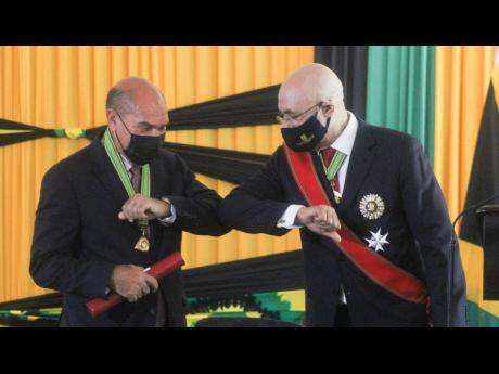 Governor General Sir Patrick Allen (right) bumps elbows with newly installed Trelawny Custos Hugh Gentles at the ceremony at the Ocean Coral Spring Hotel in Trelawny on Thursday.