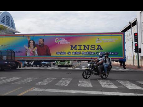 A motorcyclist rides past a truck billboard promoting President Daniel Ortega and his wife and Vice President Rosario Murillo, in Managua, Nicaragua. In recent weeks, Nicaragua President Daniel Ortega's government has rounded up 13 opposition leaders, in