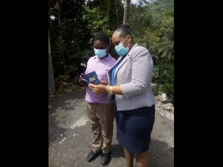 Rock River Primary School Principal Moneque McKoy-Walker gives instructions to grade six student, Ki-Jaun Brown, about his newly-acquired tablet following a presentation at the St Mary-based school.