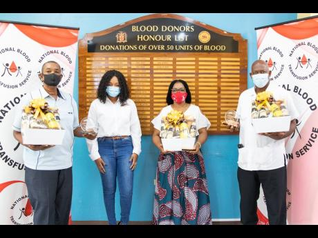 From left: World Blood Donor Day awardee, Mark Redwood, poses with Malta Brand Manager, Melissa-Kim Dunkley; Sonya Binns Lawrence, who has donated more than 100 units of blood and Franklyn White, who has donated more than 50 units.