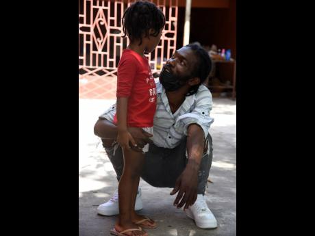 Kenrick Spencer stoops to talk to his three-year-old daughter, Tianna Spencer, at Oliver Gardens in May Pen, Clarendon, yesterday.