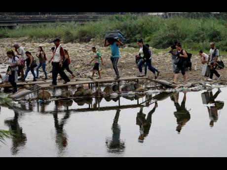 In this April 2019 photo, taken from La Parada, near Cucuta, Columbia, Venezuelans enter illegally into Colombia near the Simon Bolivar International Bridge, which is partially closed by Venezuelan authorities who are only permitting students, seniors and
