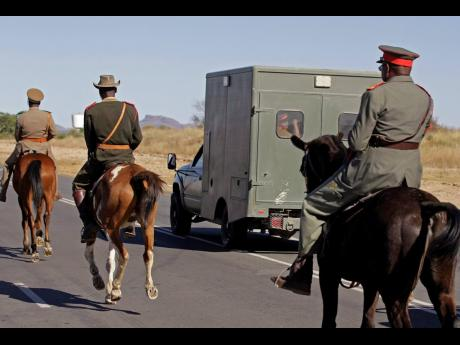 Riders on horse back escort  the small truck that is transporting skulls of ancestors recently returned from Germany, from the airport to be put on display in the city of  Windhoek, Namibia, in October 2011.