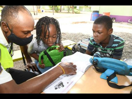Shawn Muir (left), a security guard at Liberty Academy at Priory in St Andrew, takes his sons, six-year-old Nashawn and 10-year-old Dai-Shawn, to work with him so that he may help with their online schooling.