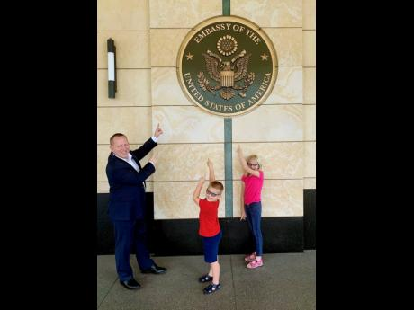 McIntyre tries to include his children in his diplomatic duties at the US Embassy. That way, they have a better understanding and will accept when daddy has to go off to work. From left: John McIntyre and children, Ian and Emma, point to the US Embassy's