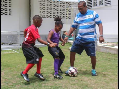 From left: Ravi Peters and his sister Rebekah try to tackle their father Richard Peters during a football game last Sunday at their home.