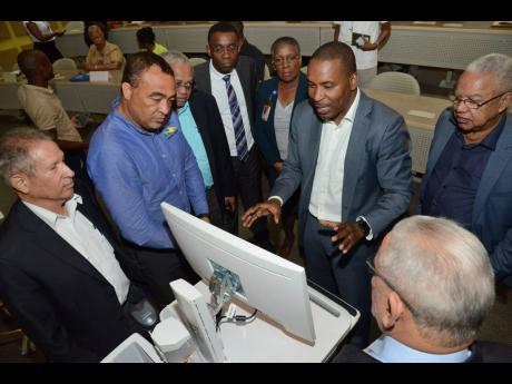 Dr Carl Bruce (third right), medical chief of staff af the University Hospital of the West Indies, shows the hospital's new information management system to health and IT specialists, (from left) Mark Thwaites, Dr Christopher Tufton, Professor Archibald