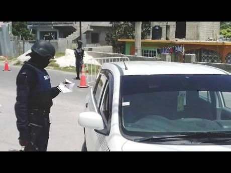 A policeman checks the documents of a motorist in Norwood, St James, on Sunday. Opposition Leader Mark Golding has raised concerns about the rotation of law-enforcement personnel in Mt Salem, which could compromise ZOSO security arrangements.