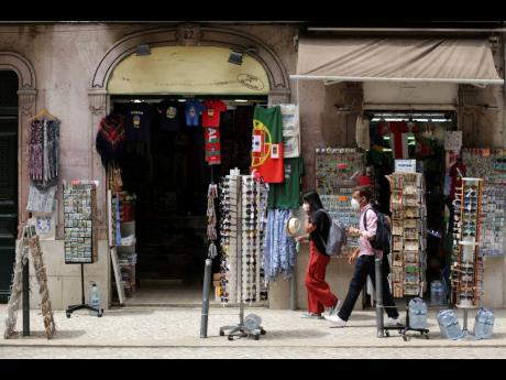 A couple wearing face masks walk past a shop selling tourist souvenirs in downtown Lisbon.