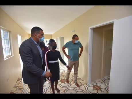 Prime Minister Andrew Holness (left) tours the three-bedroom house handed over to Charmaine Lewis (centre) in Pedro, St Catherine, on June 18. At right is St Catherine West Central Member of Parliament Dr Christopher Tufton. The house was constructed under
